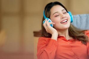porträtt av ung vacker kvinna njuter av musiken med smiley ansikte sitter i kreativa kontor eller café foto