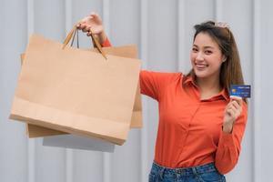 utomhus porträtt av glad kvinna med shoppingkassar med kreditkort foto