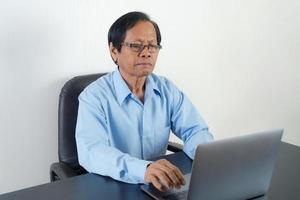 stående av den asiatiska äldre mannen som använder bärbara datorn foto