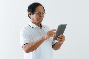 stående av den asiatiska äldre mannen som använder en digital minnestavla foto