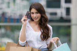 utomhus porträtt av glad kvinna med shoppingkassar och leende ansikte foto