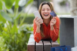 utomhus porträtt av glad kvinna med kreditkort foto