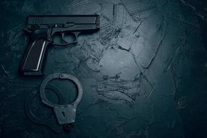 pistol och handbojor på texturerat bord foto