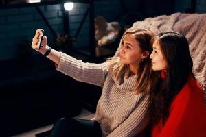 två söta tjejer i stickade tröjor tar selfies på smarttelefonen foto