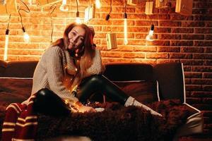 söt flicka sitter på soffan foto