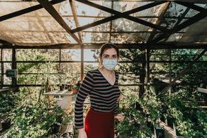 en kvinna som bär en mask som gör lite trädgårdsarbete under en super solnedgång foto
