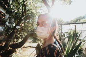 kvinna som använder en mask som ser direkt till kameran under en ljus solnedgång foto