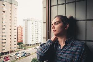 orolig kvinna som tittar från fönstret i hennes lägenhet foto