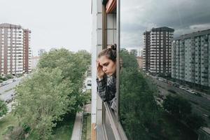 kvinna orolig vid fönstret i staden under en vårdag foto