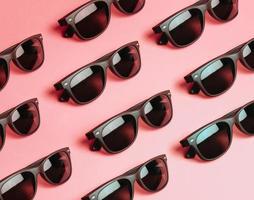 mönster av solglasögon över en pastellrosa bakgrund med kopia utrymme foto