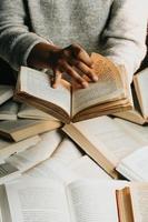 närbild av ett par händer som läser en gammal bok foto