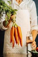 kvinna som håller morötter och grönsaker över ett bord med vatten foto