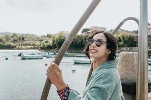 ung kvinna på en båtdocka som ler under en solig dag foto