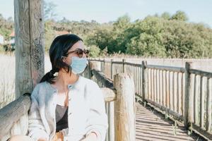 kvinna som använder solglasögon och en ansiktsmask som ler mot kameran foto