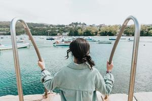 kvinna bakåt framför havet med många båtar foto