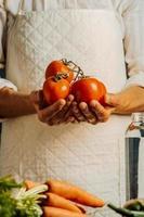 kvinna som rymmer tomater och grönsaker över ett bord med vatten foto