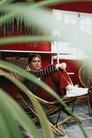 kvinnasammanträde på en bambustol som ser direkt till kameran foto