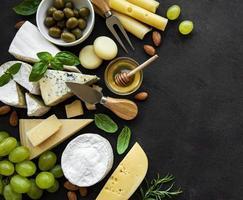 olika typer av ost, druvor, honung och snacks på svart betongbakgrund foto