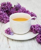 kopp te och lila blommor foto