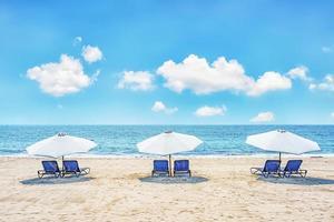 stolar och paraplyer på en tropisk strand foto