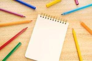 Tom anteckningsbok omgiven av färgade markörpennor på träbord foto