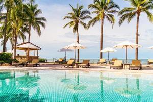 vacker tropisk strand och hav med paraply och stol runt poolen i hotellresorten foto