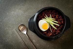 koreansk snabbnudel med svart bönsås toppad med gurka och kokt ägg foto