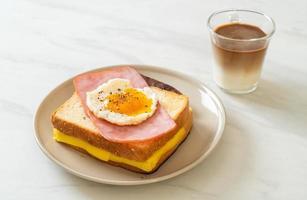 hemlagat bröd rostad ost toppad med skinka och stekt ägg med fläskkorv och kaffe till frukost foto
