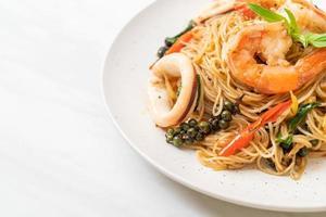 rörstekt kinesisk nudel med basilika, chili, räkor och bläckfisk - asiatisk matstil foto
