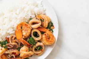ris och stekt skaldjur, räkor och bläckfisk, med thailändsk basilika - asiatisk matstil foto