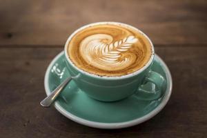 varm cappuccino med lattekonst på träbakgrund foto