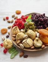 skål med olika torkade frukter och nötter foto