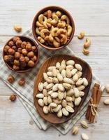 skålar med olika nötter på ett bord foto