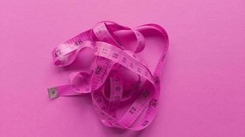 rosa centimeter på rosa bakgrund enkel platt låg med pastell textur fitness koncept stock photo foto