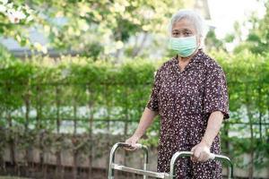 asiatisk senior eller äldre gammal damkvinnapatientpromenad med rullator i park med kopia utrymme hälsosamt starkt medicinskt koncept foto