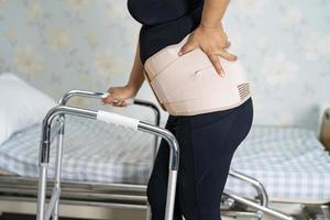 asiatisk dampatient som bär ryggvärkstödbälte för ortopedisk ländrygg med rullator foto