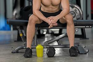 sportig man träning med hantel i gym bodybuilder sport konditionsträning foto