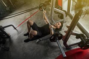 sport man träning med en tung skivstång foto