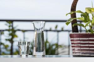drick vattenglaskanna med glas på bordet i trädgårdshemmet foto