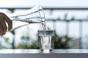 hälla dricksvatten från flaskan i glaset hemma i trädgården foto