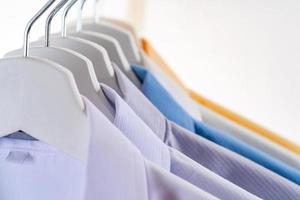 män klär skjortkläder på galgar på vit bakgrund foto
