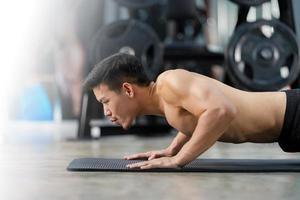 sportig man utbildning gör push ups på gymmet foto
