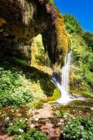 sötvatten rinner från mossa till stenar och bildar ett litet vattenfall foto
