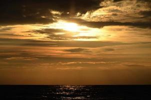 strand himmel orange toner moln och havsvågor vacker natur ljus solnedgång mörkt vatten foto