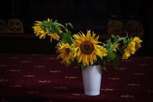 solrosor i vas som står på mörkröd matta med prydnad foto