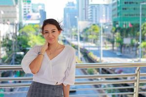 porträtt av en vacker kvinna som står i en stadsbyggnad som ler lyckligt urban livsstil foto