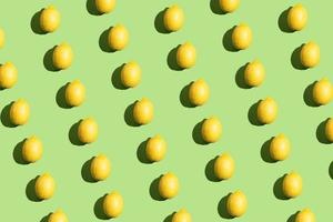 färgglada popkonst stil repetitiva mönster gjorda av citroner med hård skugga på grön bakgrund foto
