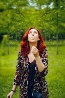 ung rödhårig kvinna blåser bort en maskros foto