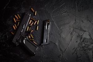 pistol med patroner på svart betongbord foto