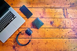 ovanifrån av bärbara trådlösa hörlurar mobiltelefon och plånbok på träbord foto